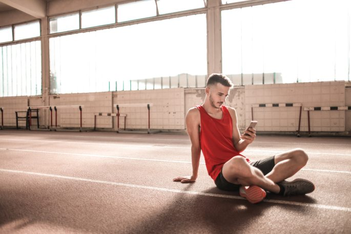 man-in-red-tank-top-and-black-shorts-sitting-on-running-3763876